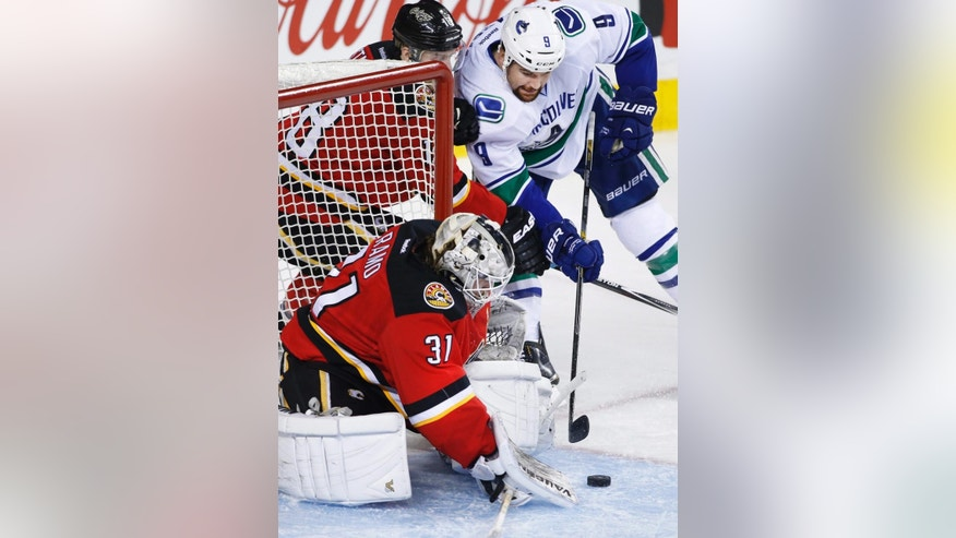 Calgary Flames goalie Karri Ramo, left, from Finland, makes a save against Vancouver Canucks' Zack Kassian during the second period of an NHL hockey game Saturday, Feb. 14, 2015, in Calgary, Alberta. (AP Photo/The Canadian Press, Larry MacDougal)