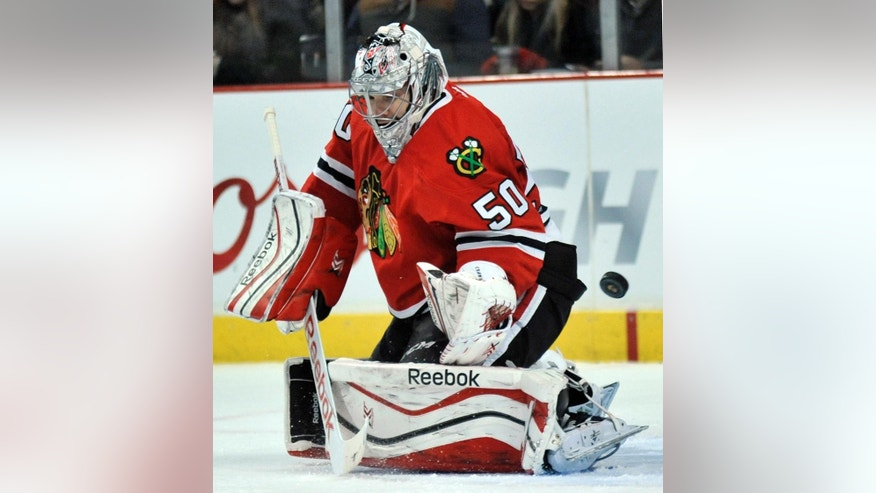 Chicago Blackhawks goalie Corey Crawford makes a save during the first period of an NHL hockey game against the Pittsburgh Penguins in Chicago, Sunday, Feb. 15, 2015. (AP Photo/Paul Beaty)