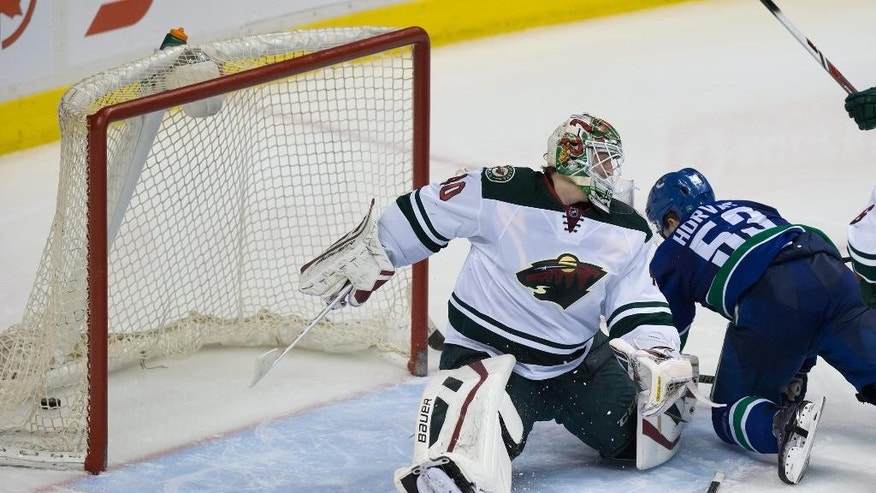 Vancouver Canucks' Bo Horvat, right, scores against Minnesota Wild goalie Devan Dubnyk during the third period in Vancouver, British Columbia, Monday, Feb. 16, 2015. (AP Photo/The Canadian Press, Darryl Dyck)