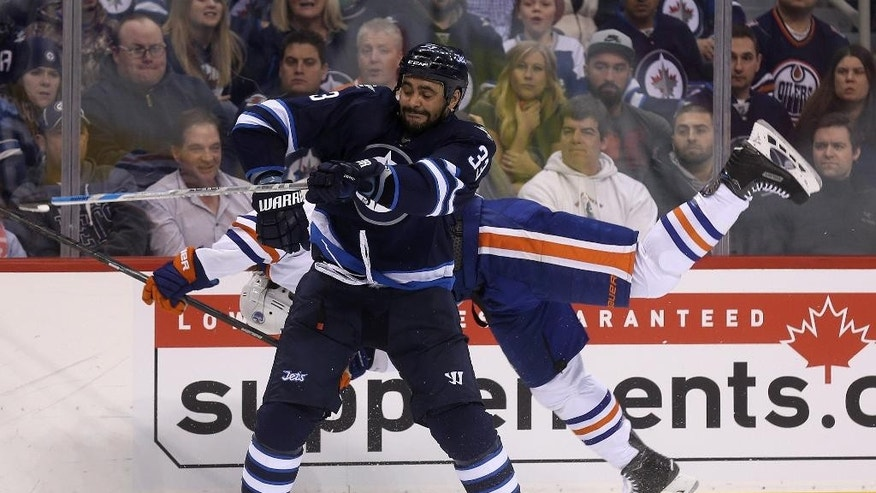 Winnipeg Jets' Dustin Byfuglien (33) hits Edmonton Oilers' Luke Gazdic (20) during second period NHL hockey action in Winnipeg, Manitoba, Monday, Feb. 16, 2015. (AP Photo/The Canadian Press, Trevor Hagan)
