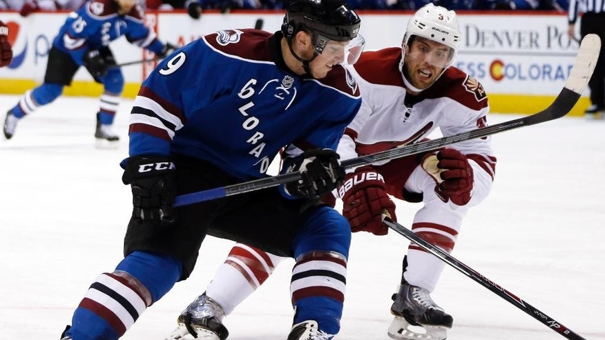 Colorado Avalanche center Matt Duchene, left, pursues the puck with Arizona Coyotes defenseman Brandon Gormley in the second period of an NHL hockey game Monday, Feb. 16, 2015, in Denver. (AP Photo/David Zalubowski)