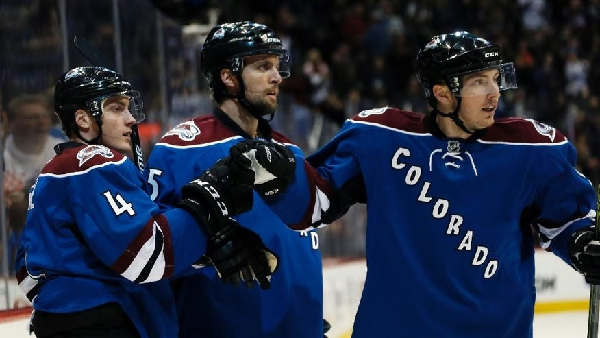 Colorado Avalanche defenseman Tyson Barrie, left, celebrates scoring a goal with defenseman Nate Guenin, center, and center Matt Duchene in the second period of an NHL hockey game against the Arizona Coyotes, Monday, Feb. 16, 2015, in Denver. (AP Photo/David Zalubowski)