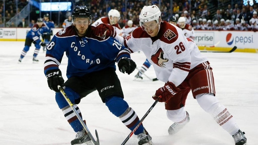 Colorado Avalanche center Paul Carey, left, pursues the puck with Arizona Coyotes defenseman Michael Stone in the second period of an NHL hockey game Monday, Feb. 16, 2015, in Denver. (AP Photo/David Zalubowski)