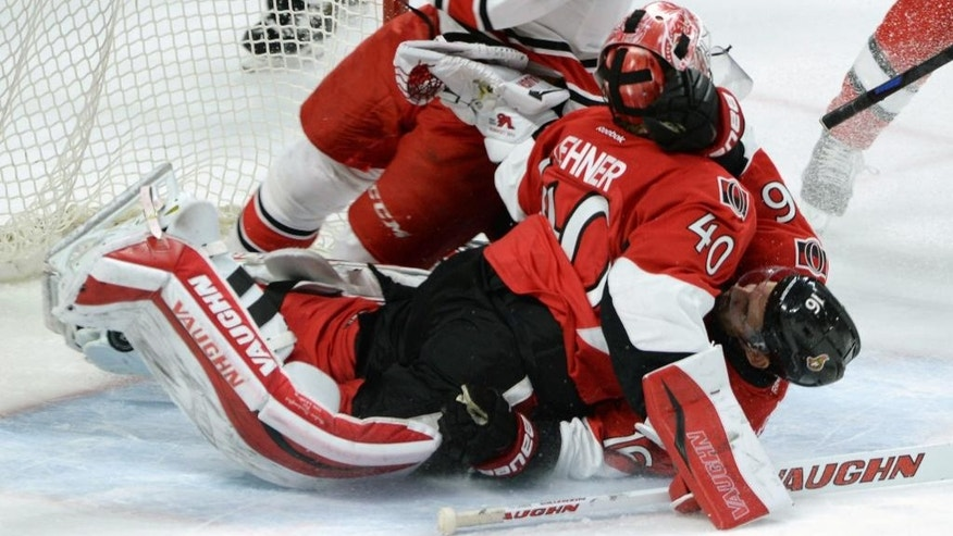 Ottawa Senators' Clarke McArthur collides with teammate Robin Lehner as they get caught up with Carolina Hurricanes' Jay McClement during the second period of an NHL game in Ottawa, Ontario, Monday, Feb 16, 2015. (AP Photo/The Canadian Press, Sean Kilpatrick)