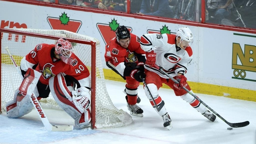 Ottawa Senators' Robin Lehner, left, looks on as teammate Mark Stone tries to knock Carolina Hurricanes' Andrej Nestrasil off the puck during the first period of an NHL game in Ottawa, Ontario, Monday, Feb 16, 2015. This will be Prince's first ever NHL game. (AP Photo/The Canadian Press, Sean Kilpatrick)