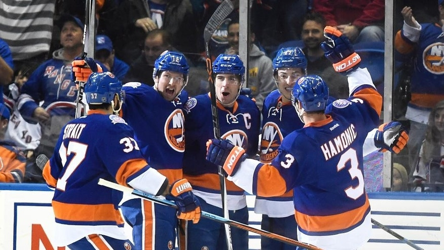 New York Islanders defenseman Brian Strait (37), Josh Bailey (12), center John Tavares (91),center Anders Lee (27) and defenseman Travis Hamonic (3) celebrate Tavares's goal in the first period of an NHL hockey game against the New York Rangers at Nassau Coliseum on Monday, Feb. 16, 2015, in Uniondale, N.Y. (AP Photo/Kathy Kmonicek)