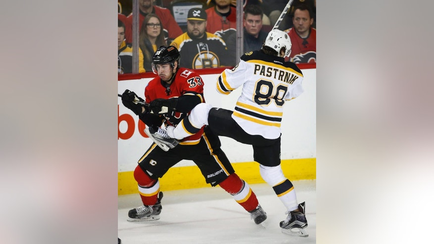 Boston Bruins David Pastrnak, right, from the Czech Republic, checks Calgary Flames Raphael Diaz, from Switzerland, during second period NHL hockey action in Calgary, Alberta, Monday, Feb. 16, 2015. (AP Photo/The Canadian Press, Jeff McIntosh)