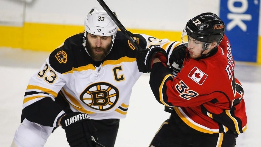 Boston Bruins Zdeno Chara, left, from Slovakia, checks Calgary Flames Paul Byron during first period NHL hockey action in Calgary, Alberta,  Monday, Feb. 16, 2015. (AP Photo/The Canadian Press, Jeff McIntosh)