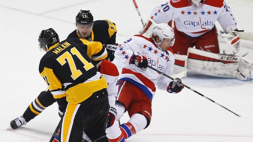 Pittsburgh Penguins' Blake Comeau (17), top, trips Washington Capitals' Nicklas Backstrom in the first period of an NHL hockey game, Tuesday, Feb. 17, 2015, in Pittsburgh. Comeau was penalized on the play. (AP Photo/Keith Srakocic)