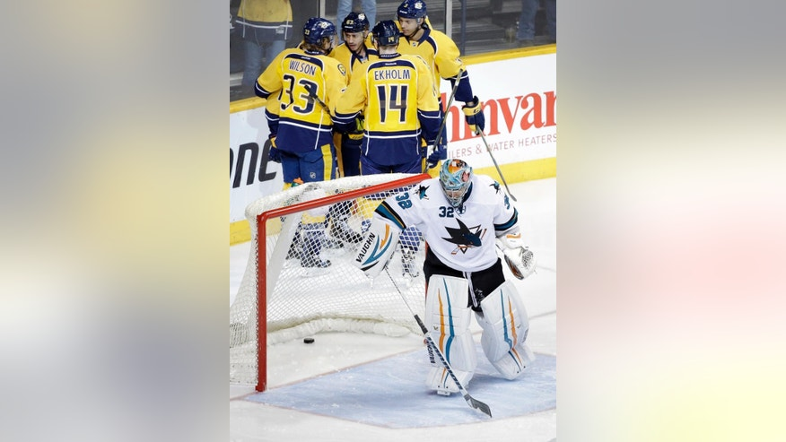 San Jose Sharks goalie Alex Stalock (32) skates away from the net as Nashville Predators players celebrate a goal by Craig Smith in the second period of an NHL hockey game Tuesday, Feb. 17, 2015, in Nashville, Tenn. (AP Photo/Mark Humphrey)