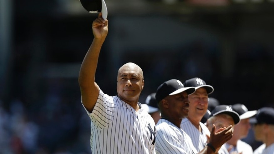 FILE - This June 23, 2013 file photo shows former New York Yankees outfielder Bernie Williams waving his cap as he is introduced before the Yankees Old Timers Day baseball game at Yankee Stadium in New York. The Yankees are retiring the uniform numbers of Andy Pettitte, Jorge Posada and Bernie Williams and will honor the trio with plaques in Monument Park this season along with Willie Randolph. Williams will be honored before the May 24 game against Texas. (AP Photo/Kathy Willens, file)