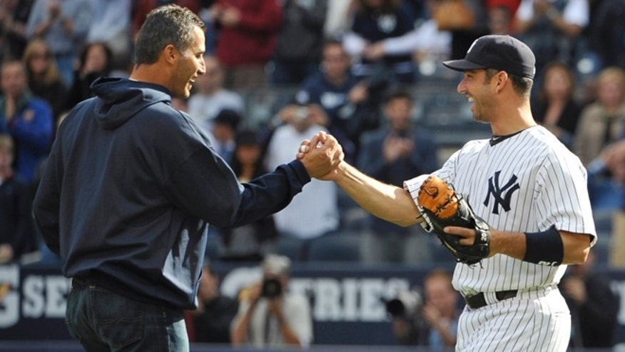 FILE - This Oct. 2, 2011 file photo shows  former New York Yankees pitcher Andy Pettitte, left, shaking hands with Jorge Posada after Pettitte threw out the first ceremonial pitch at Yankee Stadium in New York. The Yankees are retiring the uniform numbers of Andy Pettitte, Jorge Posada and Bernie Williams and will honor the trio with plaques in Monument Park this season along with Willie Randolph. Posada's ceremony will be on Aug. 22, followed by Pettitte's the next day. (AP Photo/Kathy Kmonicek, file)
