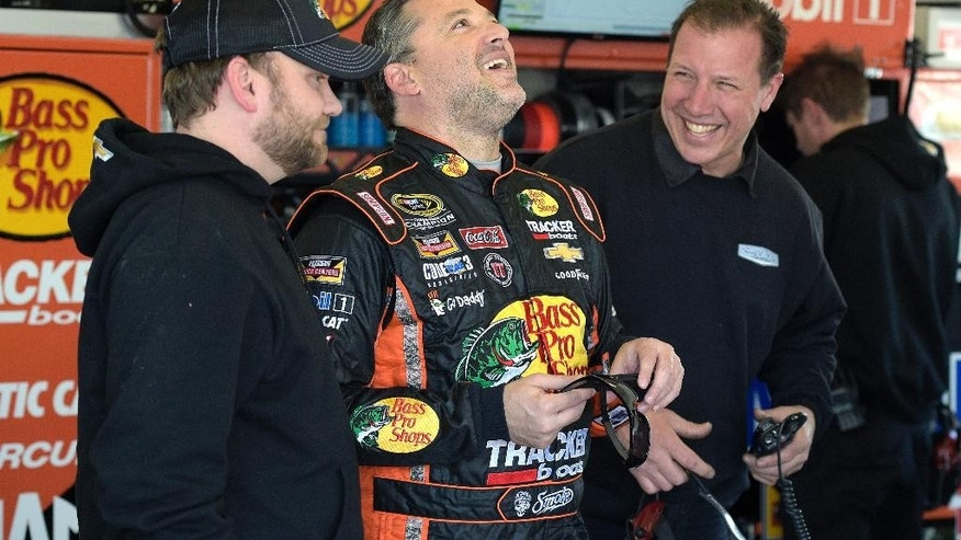 Driver Tony Stewart, center, has a laugh with his crew in the garage during a practice session for the Daytona 500 NASCAR Sprint Cup Series auto race at Daytona International Speedway, Saturday, Feb. 14, 2015, in Daytona Beach, Fla.(AP Photo/Phelan M. Ebenhack)
