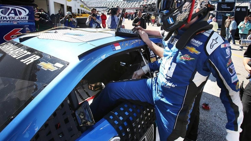 Dale Earnhardt Jr. climbs into his race car during Sprint Cup practice for the Daytona 500 at Daytona International Speedway in Daytona Beach, Fla. on Wednesday, Feb. 18, 2015. (AP Photo/Orlando Sentinel, Stephen M. Dowell) MAGS OUT; NO SALES