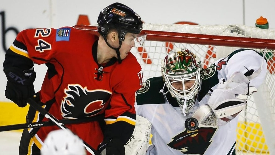 Minnesota Wild goalie Devan Dubnyk, right, grabs for the puck as Calgary Flames Jiri Hudler, from the Czech Republic, looks on during the second period of an NHL hockey game, Wednesday, Feb. 18, 2015 in Calgary, Alberta.  (AP Photo/Canadian Press, Jeff McIntosh)