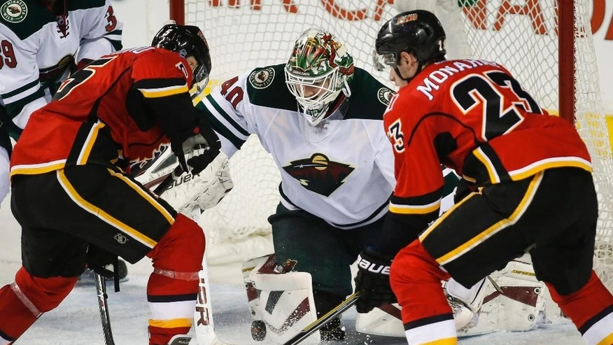 Minnesota Wild goalie Devan Dubnyk, center, pounces on the puck as Calgary Flames Mark Giordano, left, and Sean Monahan try to score during the second period of an NHL hockey game, Wednesday, Feb. 18, 2015 in Calgary, Alberta.  (AP Photo/Canadian Press, Jeff McIntosh)