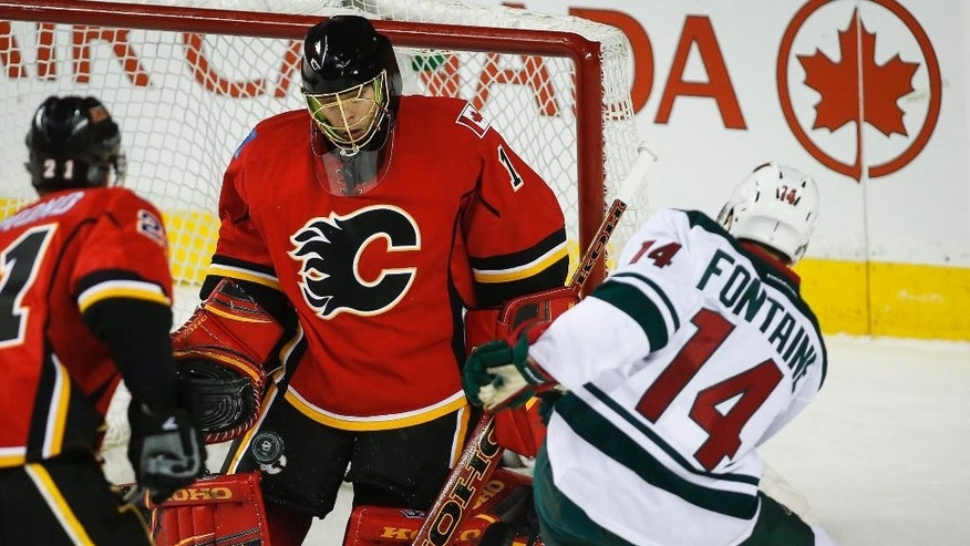 Minnesota Wild Justin Fontaine, right, scores on Calgary Flames goalie Jonas Hiller, from Switzerland, during the first period of an NHL hockey game, Wednesday, Feb. 18, 2015 in Calgary, Alberta.  (AP Photo/Canadian Press, Jeff McIntosh)
