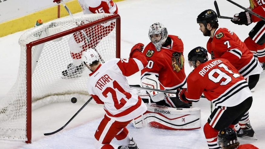 Detroit Red Wings left wing Tomas Tatar (21) scores past Chicago Blackhawks goalie Corey Crawford (50) as Brent Seabrook (7), Brad Richards (91) and Patrick Kane (88) watch during the second period of an NHL hockey game Wednesday, Feb. 18, 2015, in Chicago. (AP Photo/Charles Rex Arbogast)