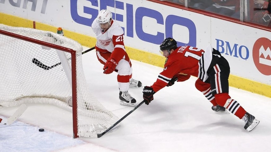 Chicago Blackhawks center Jonathan Toews (19) is unable to score a wrap around goal as Detroit Red Wings left wing Tomas Tatar (21) watches during the second period of an NHL hockey game Wednesday, Feb. 18, 2015, in Chicago. (AP Photo/Charles Rex Arbogast)
