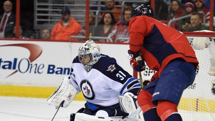 Winnipeg Jets goalie Ondrej Pavelec (31), of The Czech Republic, looks for the puck against Washington Capitals left wing Alex Ovechkin, right, of Russia, during the second period of an NHL hockey game, Thursday, Feb. 19, 2015, in Washington. (AP Photo/Nick Wass)
