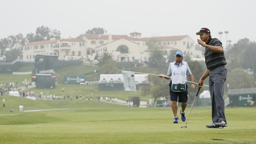 Retief Goosen of South Africa waves after making a birdie on the 10th hole as the clubhouse is seen behind him during the first round of the Northern Trust Open golf tournament at Riviera Country Club in the Pacific Palisades area of Los Angeles on Thursday, Feb. 19, 2015. (AP Photo/Danny Moloshok)