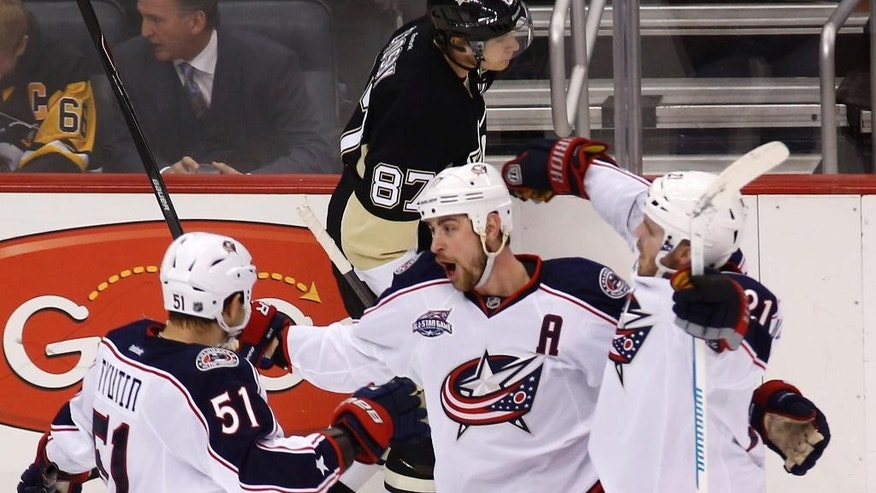 Columbus Blue Jackets' Brandon Dubinsky, center, celebrates with teammate Fedor Tyutin (51) and James Wisniewski (21) after scoring as Pittsburgh Penguins' Sidney Crosby (87) skates behind them in the third period of an NHL hockey game, Thursday, Feb. 19, 2015, in Pittsburgh. The goal proved to me the margin of victory as the Blue Jackets won 2-1. (AP Photo/Keith Srakocic)