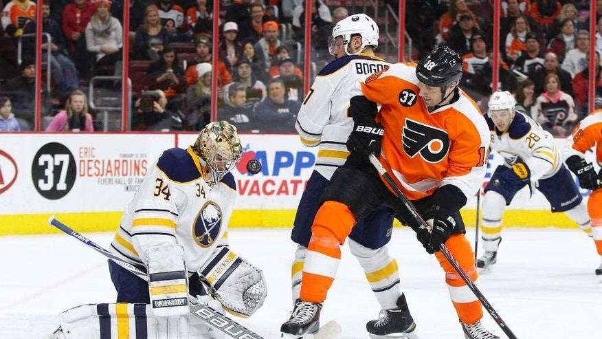Buffalo Sabres goalie Michal Neuvirth, left, of Czech Republic makes the initial save as defenseman Zach Bogosian, center, deals with Philadelphia Flyers left wing R.J. Umberger, right, who is looking for the rebound during the second period of an NHL hockey game, Thursday, Feb. 19, 2015, in Philadelphia. (AP Photo/Chris Szagola)