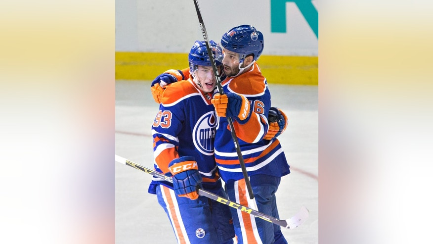 Edmonton Oilers' Ryan Nugent-Hopkins (93) and David Krejci (46) celebrate a goal against the Boston Bruins during the second period of an NHL hockey game Wednesday, Feb. 18, 2015, in Edmonton, Alberta. (AP Photo/The Canadian Press, Jason Franson)
