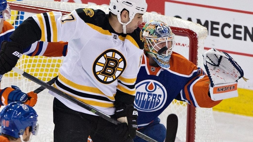 Boston Bruins' Milan Lucic (17) screens Edmonton Oilers goalie Ben Scrivens (30) as Scrivens makes a save during the second period of an NHL hockey game Wednesday, Feb. 18, 2015, in Edmonton, Alberta. (AP Photo/The Canadian Press, Jason Franson)