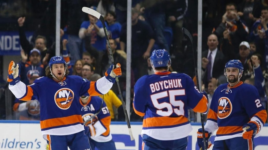 New York Islanders Michael Grabner, left, celebrates with New York Islanders defenseman Johnny Boychuk (55) and New York Islanders defenseman Nick Leddy (2) after Boychuck scored the Islanders second goal in the first period of an NHL hockey game against the Nashville Predators  at Nassau Coliseum in Uniondale, N.Y., Thursday, Feb. 19, 2015. (AP Photo/Kathy Willens)