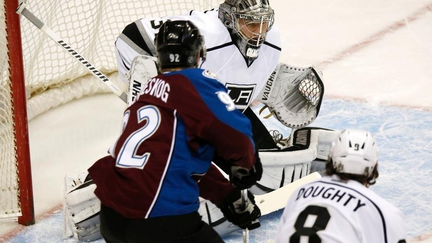 Los Angeles Kings goalie Jonathan Quick, back, stops a shot off the stick of Colorado Avalanche left wing Gabriel Landeskog, center, of Sweden, as Kings defenseman Drew Doughty covers in the first period of an NHL hockey game Wednesday, Feb. 18, 2015, in Denver. (AP Photo/David Zalubowski)