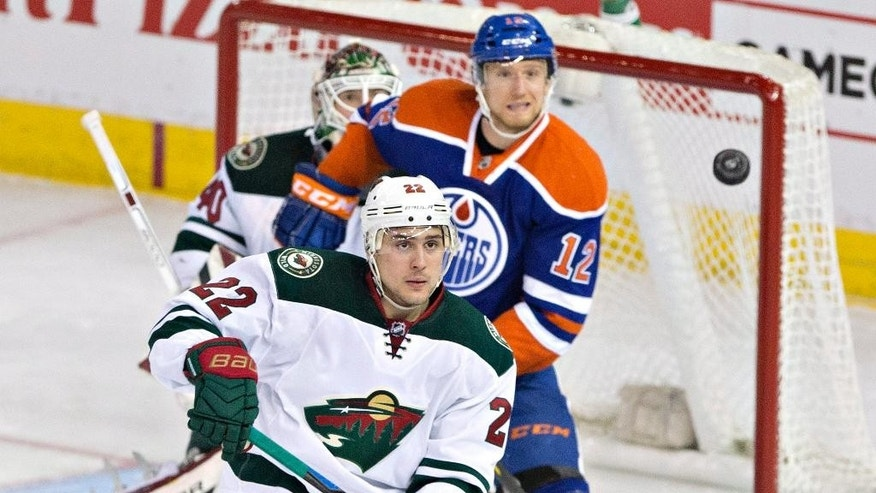 Minnesota Wild's Nino Niederreiter (22) and goalie Devan Dubnyk (40) and Edmonton Oilers' Rob Klinkhammer (12) look for the loose puck during the second period of an NHL hockey game Friday, Feb. 20, 2015, in Edmonton, Alberta. (AP Photo/The Canadian Press,  Jason Franson)