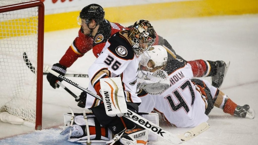 Anaheim Ducks goalie John Gibson, front, deflects the puck as teammate Hampus Lindholm, right, from Sweden, crashes into Calgary Flames' Lance Bouma during the third period of an NHL hockey game Friday, Feb. 20, 2015, in Calgary, Alberta. (AP Photo/The Canadian Press, Jeff McIntosh)