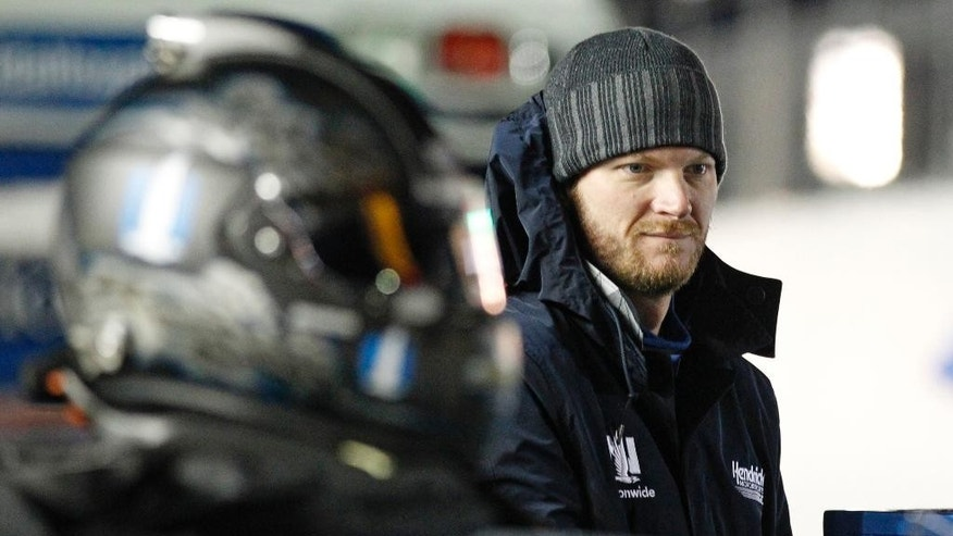 Dale Earnhardt Jr. tries to keep warm as he stands by his car before the first of two qualifying races for the Daytona 500 NASCAR Sprint Cup series auto race at Daytona International Speedway in Daytona Beach, Fla., Thursday, Feb. 19, 2015. (AP Photo/Terry Renna)