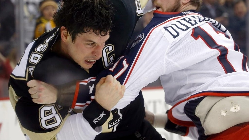 Pittsburgh Penguins' Sidney Crosby, left and Columbus Blue Jackets' Brandon Dubinsky are seen through the dasher board glass as they exchange blows in a fight in the second period of an NHL hockey game, Thursday, Feb. 19, 2015 in Pittsburgh. (AP Photo/Keith Srakocic)
