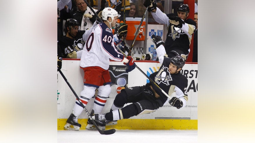 Columbus Blue Jackets' Jared Boll (40) knocks Pittsburgh Penguins' Steve Downie (23) down along the boards in the second period of an NHL hockey game, Thursday, Feb. 19, 2015 in Pittsburgh. Boll was penalized on the play. (AP Photo/Keith Srakocic)