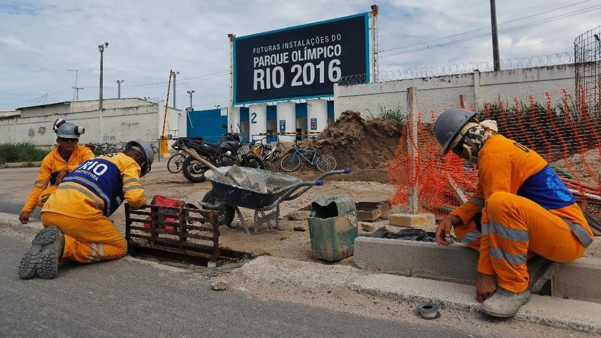 "Men work in front of a the Olympic Park's entrance, that reads in Portuguese: ""Future facilities of the Olympic Park Rio 2016,"" in Rio de Janeiro, Brazil Thursday, Feb. 19, 2015. International Olympic Committee inspectors will start a tour of facilities next week. (AP Photo/Leo Correa)"