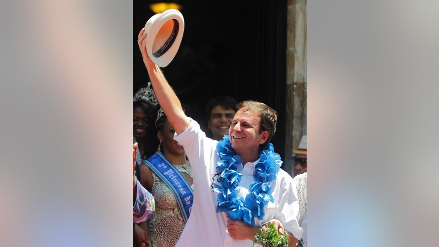 In this Feb. 13, 2015 photo, Rio de Janeiro's Mayor Eduardo Paes holds up his hat during a ceremony marking the start of Carnival in Rio de Janeiro, Brazil. A Rio de Janeiro public prosecutor opened an inquiry on Feb. 6, 2015 into alleged misconduct by Paes over the construction of the golf course for the 2016 Olympics in a nature reserve. (AP Photo/Leo Correa)