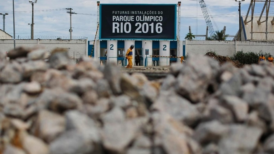 "A worker walks past one of the entrances of the Olympic Park, that reads in Portuguese ""Future facilities of the Olympic Park Rio 2016,"" in Rio de Janeiro, Brazil, Thursday, Feb. 19, 2015. International Olympic Committee inspectors will start a tour of facilities next week. (AP Photo/Leo Correa)"