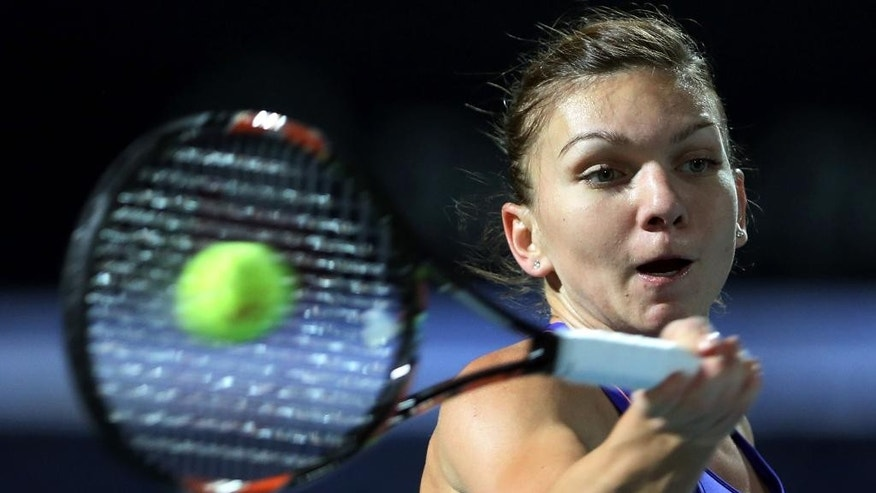 Simona Halep of Romania returns the ball to Caroline Wozniacki of Denmark during a semi final match of the Dubai Duty Free Tennis Championships in Dubai, United Arab Emirates, Friday, Feb. 20, 2015. (AP Photo/Kamran Jebreili)