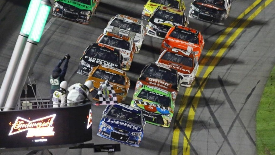 Jimmie Johnson, front, takes the checkered flag to win the second of two qualifying races for the Daytona 500 NASCAR Sprint Cup series auto race at Daytona International Speedway in Daytona Beach, Fla., Thursday, Feb. 19, 2015. (AP Photo/David Graham)