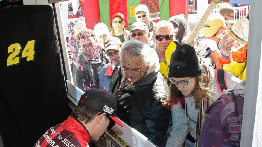 Jeff Gordon signs autographs for fans during practice for the Daytona 500 NASCAR Sprint Cup series auto race at Daytona International Speedway in Daytona Beach, Fla., Friday, Feb. 20, 2015. (AP Photo/Darryl Graham)