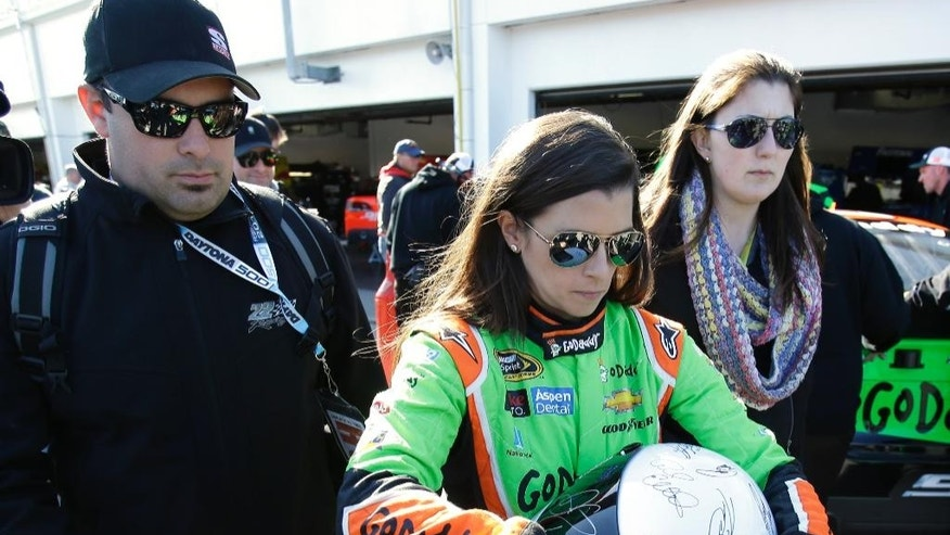 Danica Patrick signs autographs as she leaves her garage after a practice for the Daytona 500 NASCAR Sprint Cup Series auto race at Daytona International Speedway, Friday, Feb. 20, 2015, in Daytona Beach, Fla. (AP Photo/John Raoux)