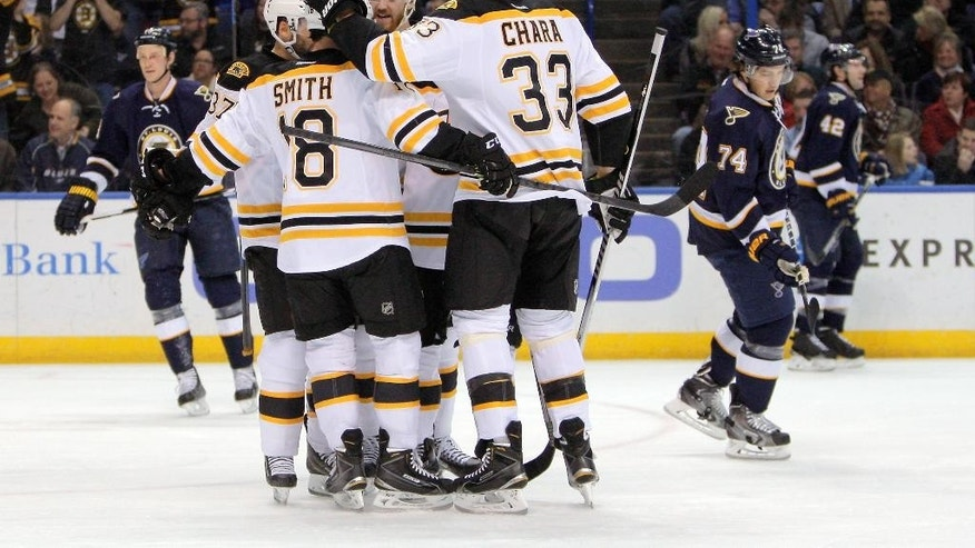 Members of the Boston Bruins celebrate a goal scored by left wing Brad Marchand during the first period of an NHL hockey game against the St. Louis Blues  Friday, Feb. 20, 2015, in St. Louis. (AP Photo/Scott Kane)