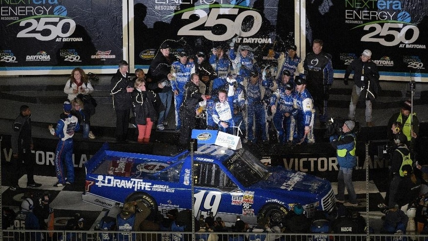 Tyler Reddick, center, celebrates in Victory Lane after winning the NASCAR Trucks series auto race at Daytona International Speedway, Friday, Feb. 20, 2015, in Daytona Beach, Fla.(AP Photo/Phelan M. Ebenhack)
