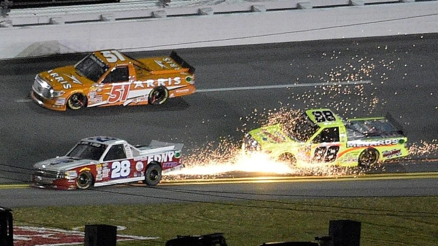 Ryan Ellis (28) sends sparks flying in front of Matt Crafton (88), while dropping to the low part of the track, as Daniel Suarez (51) drives past in Turn 4 during the NASCAR Trucks series auto race at Daytona International Speedway, Friday, Feb. 20, 2015, in Daytona Beach, Fla. (AP Photo/Phelan M. Ebenhack)