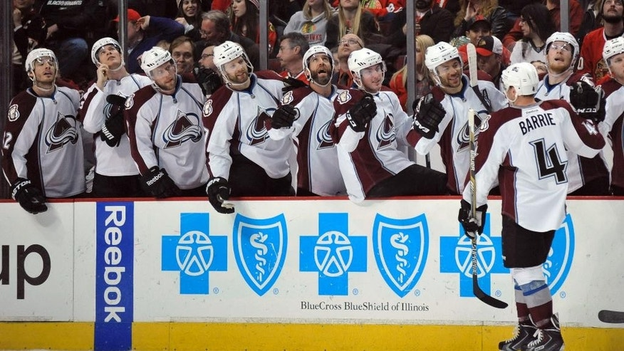 Colorado Avalanche's Tyson Barrie (4), celebrates with teammates on the bench after scoring a goal during the first period of an NHL hockey game against the Chicago Blackhawks in Chicago, Friday, Feb. 20, 2015. (AP Photo/Paul Beaty)