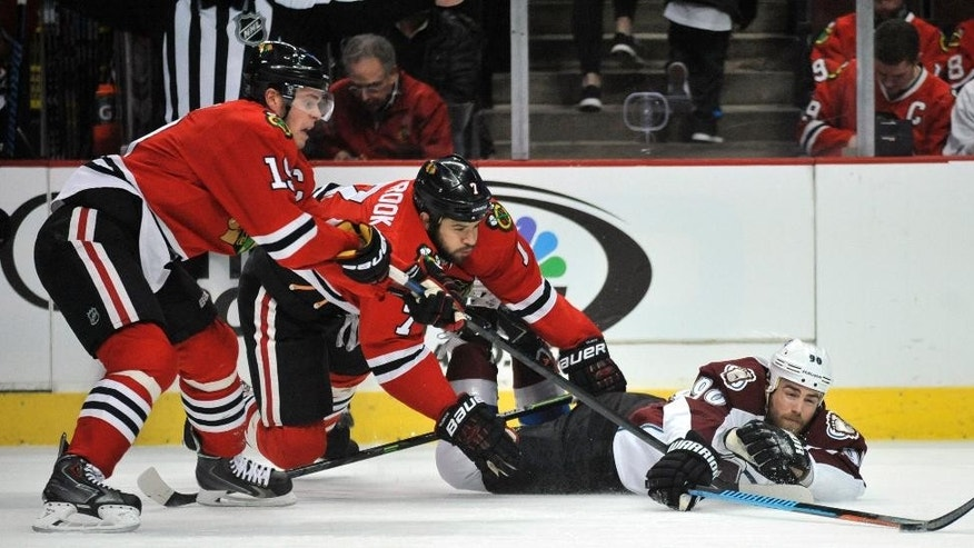Colorado Avalanche's Ryan O'Reilly, right, battles Chicago Blackhawks' Brent Seabrook, middle, and Jonathan Toews for a loose puck during the first period of an NHL hockey game in Chicago, Friday, Feb. 20, 2015. (AP Photo/Paul Beaty)