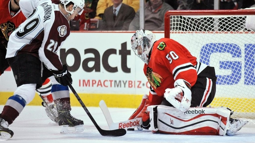 Chicago Blackhawks goalie Corey Crawford (50) makes a save against Colorado Avalanche's Nathan MacKinnon (29) during the first period of an NHL hockey game in Chicago, Friday, Feb. 20, 2015. (AP Photo/Paul Beaty)