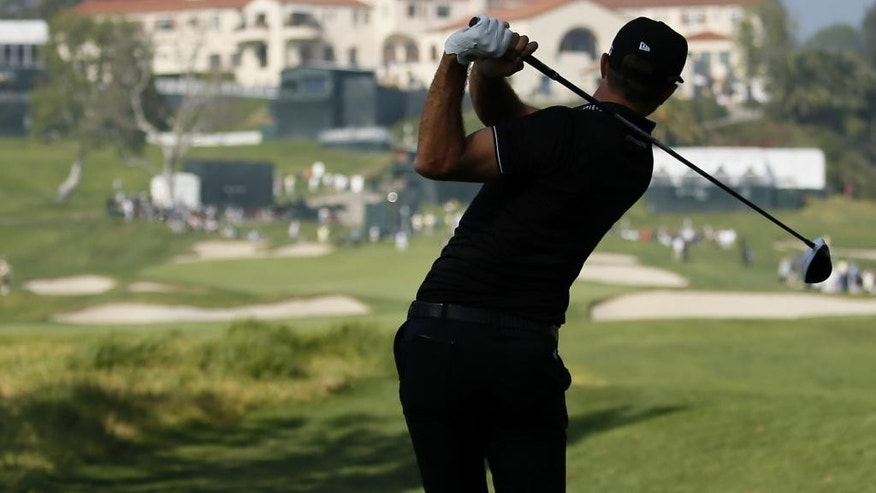 Dustin Johnson tees off on the ninth hole as the clubhouse is seen in the distance during the first round of the Northern Trust Open golf tournament at Riviera Country Club in Los Angeles, Thursday, Feb. 19, 2015. (AP Photo/Danny Moloshok)